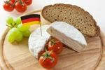 Thumbnail German Camembert chees on a board with grapes, bread and tomatoes