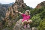 Thumbnail 7-year-old girl in the Red rocks of Piana at the Gulf of Porto, Calanche, Corsica, France, Europe