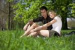 Thumbnail Young couple sitting on a picnic blanket under a tree in a park in spring