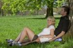 Thumbnail Young couple sitting on a picnic blanket and leaning against a tree in a park in spring
