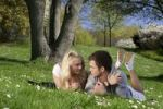 Thumbnail Young couple lying on a lawn in a park, spring