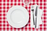 Thumbnail Set table with a plate, a glass, a knife and a fork on a red and white checkered tablecloth