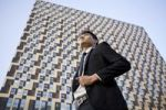 Thumbnail Low angle view of businessman standing in front of a high building, China, Asia