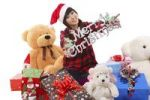 "Thumbnail Young Asian woman sitting amidst Christmas presents, lettering ""Merry Christmas"", China, Asia"