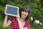Thumbnail Young woman, 25, holding a blackboard in her hands