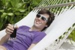 Thumbnail Young man relaxing in a hammock, holding a drink, Maldives, Indian Ocean
