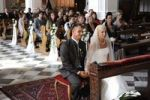 Thumbnail Bridal couple sitting in church in front of the wedding party