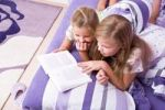 Thumbnail Two girls, sisters reading in bed