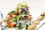 Thumbnail Salmon filet with scampi on a bed of spinach with potatoes in their skins and creamy wine sauce