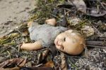 Thumbnail Old broken doll lying in the dirt on the ground