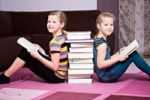 Thumbnail Girls, 11 and 8, leaning against a stack of books