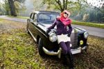 Thumbnail Young woman in front of a post-war classic car