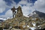Thumbnail mountaineer at stone pile on 5237 m high peak with some snow Phu Nar-Phu Annapurna Region Nepal