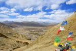 Thumbnail View into barren valley with colourful prayer flags in the wind Shegar Tibet China