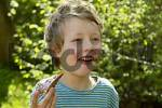 Thumbnail One seven-year-old boy eating a chocolate bread