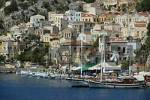 Thumbnail View of the colourful ochre houses with sailing boats in the harbour Island of Symi Greece