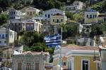 Thumbnail Greek flag blows in the wind above the colourful ochre houses Island of Symi Greece