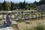 Thumbnail Ancient Greece active seniors woman is sitting in front of a row of standing pillars and a forest of slim cypress trees in the background Asklepieion Island of Kos Greece