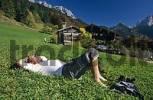 Thumbnail hiker resting in meadow at farmhouse Hinterkaiser in valley Kaisertal Tyrol Austria