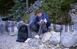 Thumbnail Young woman is sitting on an rock and reads in a hiking guide