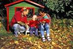 Thumbnail Mother - father - and two-year-old boy in front of a toy house in autumn MR