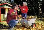 Thumbnail Father and two-year-old boy in front of a toy house in autumn MR