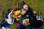 Thumbnail eight and ten year old boys lying on father at a snack during hiking