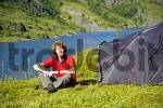 Thumbnail MR Young man sits at his tent in the wilderness of Moskenesoya with Agvatnet Lofoten Norway