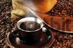Thumbnail Coffee in a brown cup with ground coffee atop a bed of coffee beans