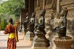 Thumbnail Young monk walks along old Buddha statues temple Haw Pha Kaew Vientiane Laos