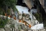 Thumbnail Row of orange dressed monks at Pak Ou cave near Luang Prabang Laos