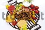 Thumbnail Fried bratwurst sausages on a grill with fresh peppers, tomatoes and assorted BBQ sauces