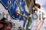 Thumbnail Graffity sprayer with breathing protection at work in Munich in railway underpass
