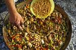 Thumbnail chickpeas are added while cooking a Paella in a pan, spanish speciality, Spain