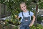 Thumbnail Girl, 5, standing under a small apple tree