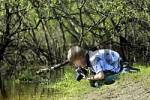 Thumbnail 10 year old boy observing life in the water and photographing on a pond edge
