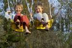 Thumbnail eight-year-old and ten-year-old boys swinging happy