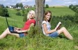 Thumbnail Two teenage girls, leaning against a tree stump with laptop and book