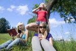 Thumbnail Three teenage girls with mobile phones and a book in meadow