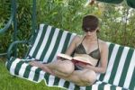 Thumbnail Young woman sitting on a garden swing reading a book