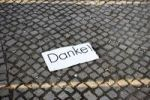 Thumbnail A slip of paper reading Danke!, Thanks, lying on a cobbled street