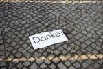 Thumbnail A slip of paper reading Danke!, Thanks, lying on a cobbled street