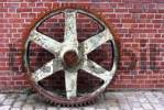 Thumbnail old rusted cog wheel in front of a brick wall