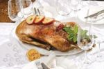 Thumbnail Roast goose with apple rings on a festively decorated table