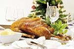 Thumbnail Roast goose, dumplings on a festively decorated table, in the back a decorated christmas tree