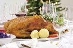 Thumbnail Roast goose, red cabbage, dumplings on a festively decorated table, in the back a decorated christmas tree