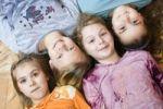 Thumbnail Group of four little girls lying on the floor, from the left 6, 11, 9 and 10 years old, birds-eye view