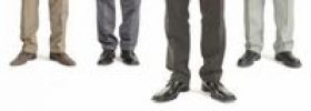 Thumbnail Four businessmen standing in a row with one standing further forward, detail of legs