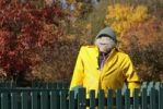Thumbnail Scarecrow with a yellow rain jacket in front of a colourful autumnal forest
