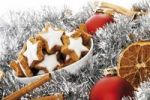 Thumbnail Cinnamon flavored star-shaped biscuits in a white bowl, christmas decorations, cinnamon sticks, orange slices and christmas tree balls